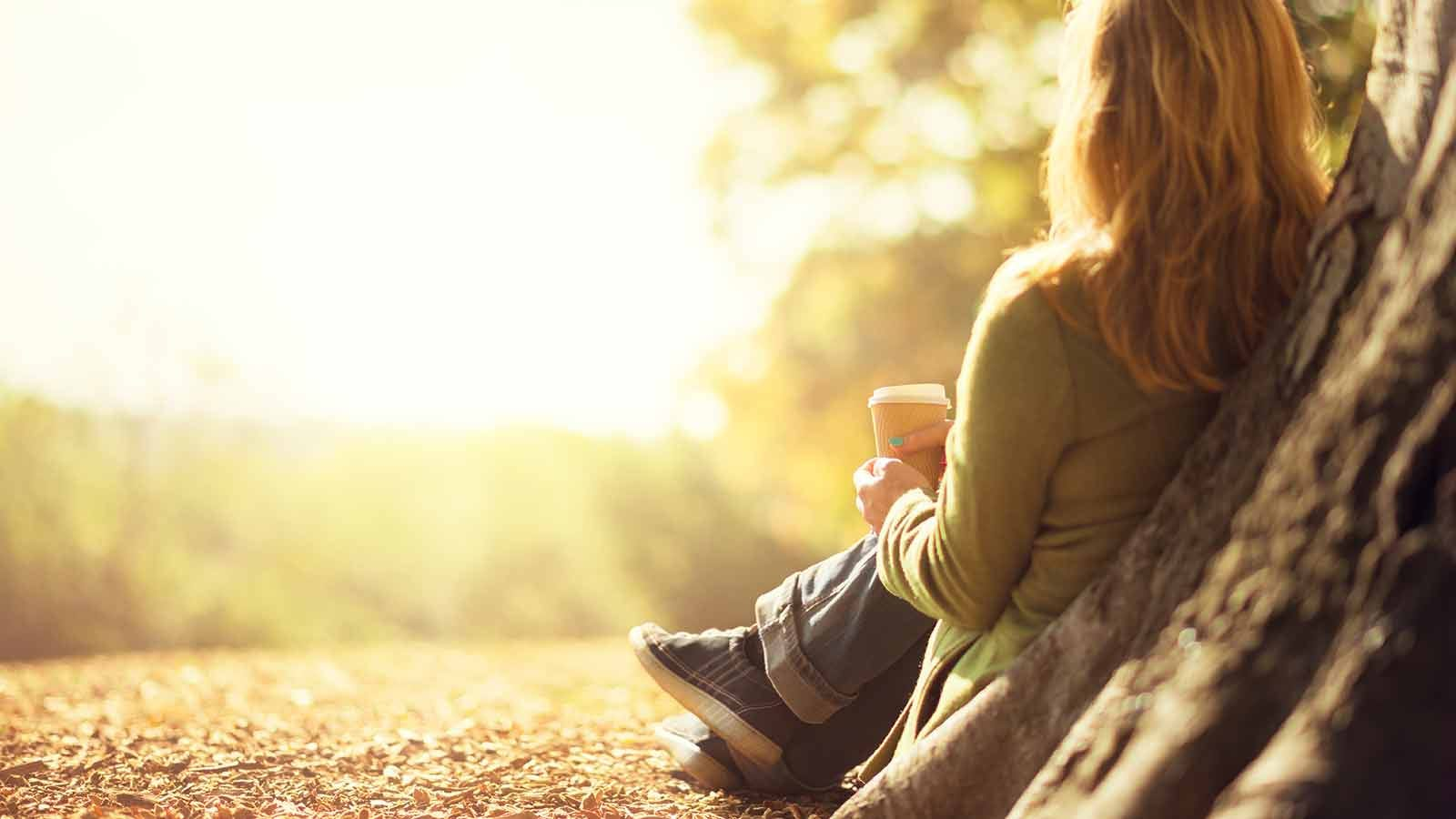 Woman sitting under a tree drinking a cup of coffee.