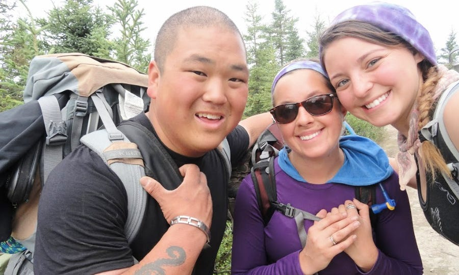 A man and two women wearing backpacks.