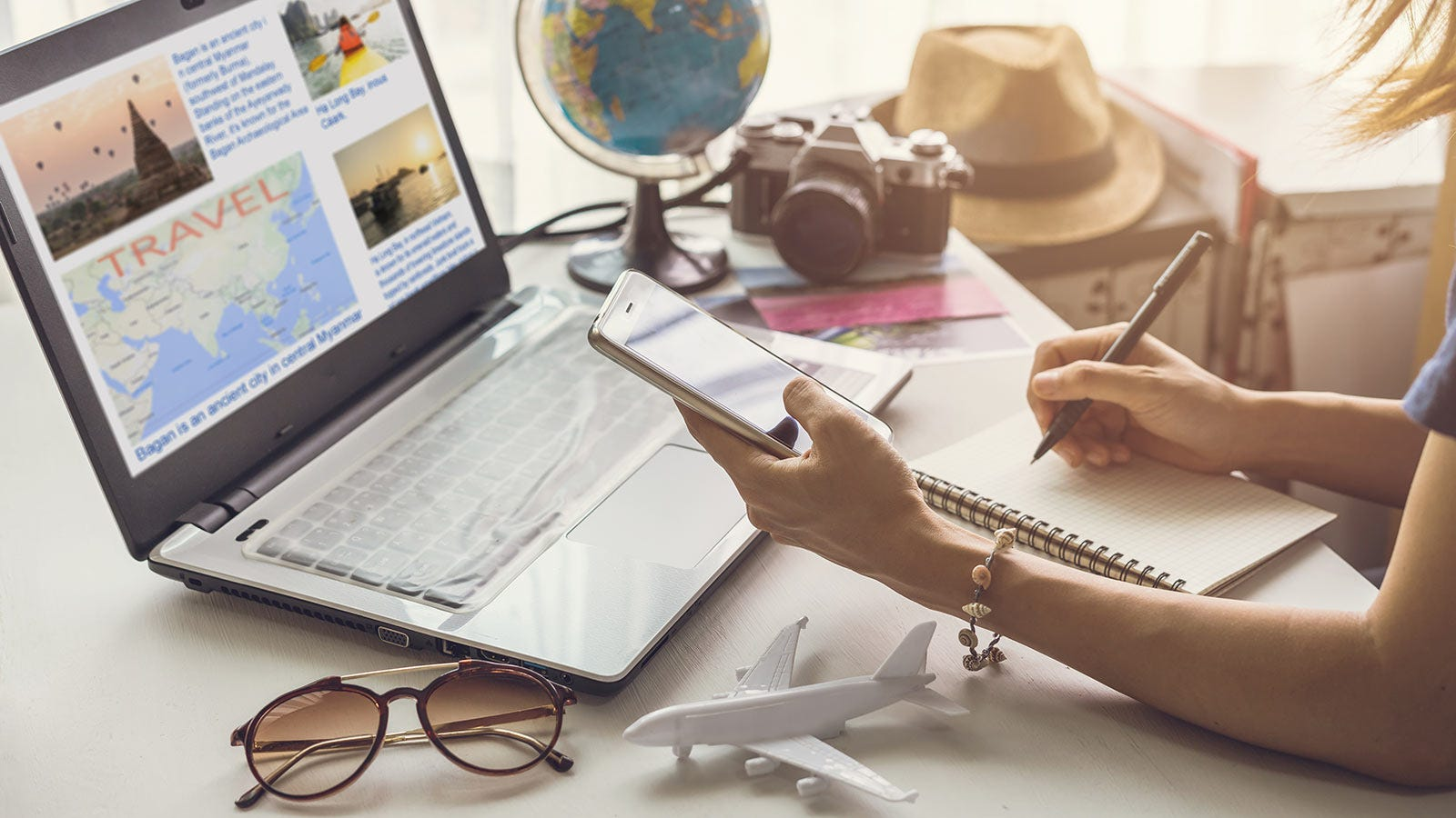 A woman jotting down travel ideas from a website in a notebook.