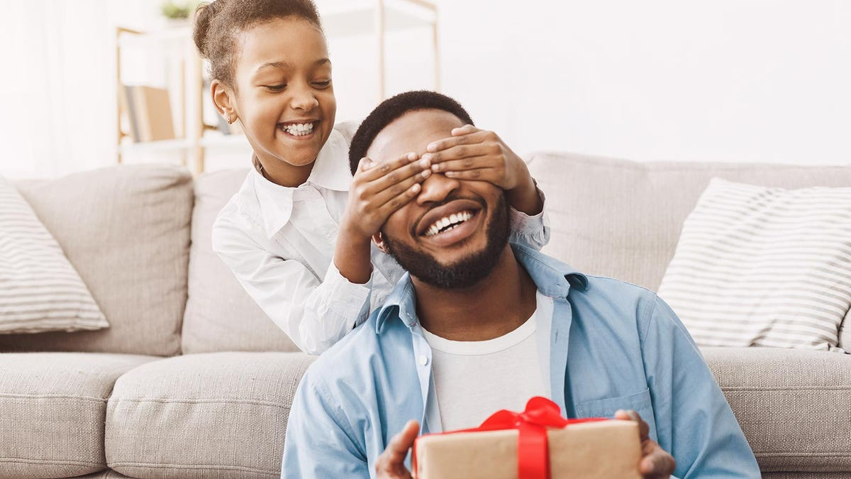 Young daughter giving her dad a present on Father's Day.