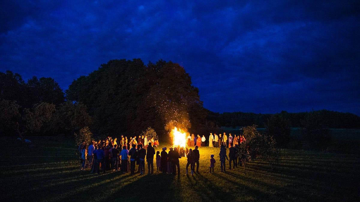 People standing around a midsummer solstice bonfire.