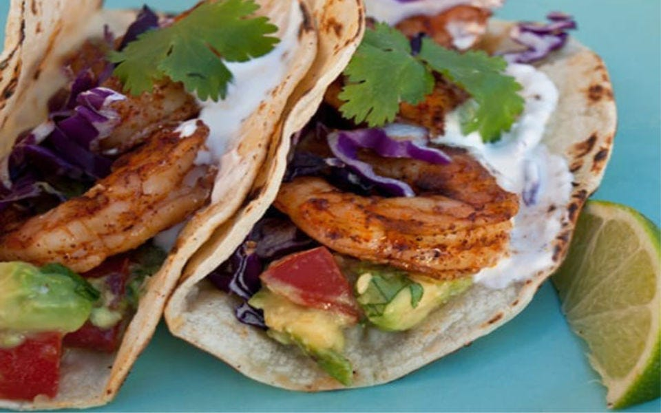 Two tacos stuffed with grilled shrimp and avocado salsa next to a slice of lime.