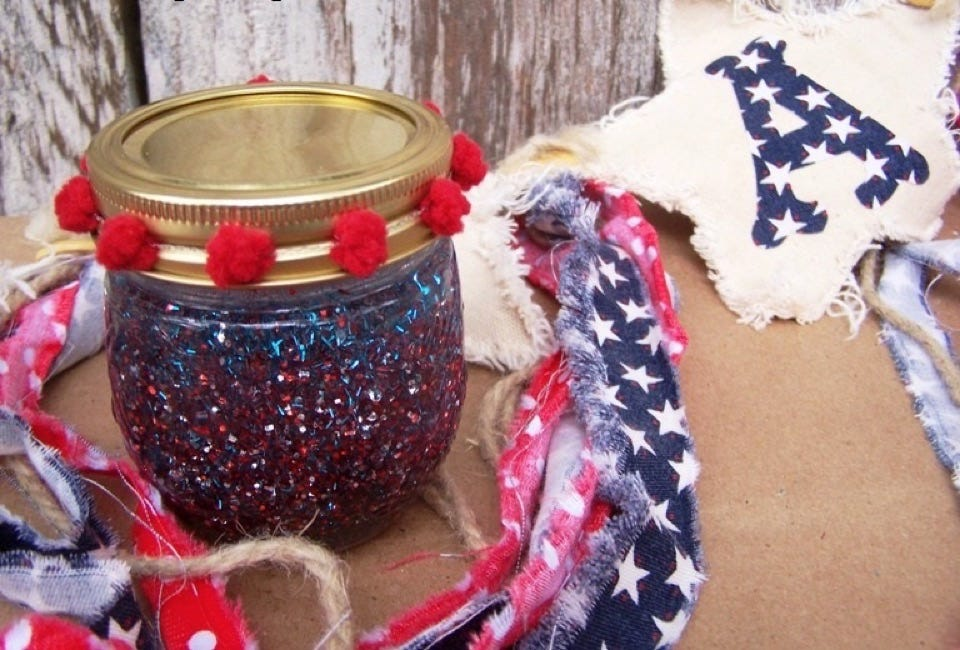 A glass jar full of glitter surrounded by Fourth of July decorations.