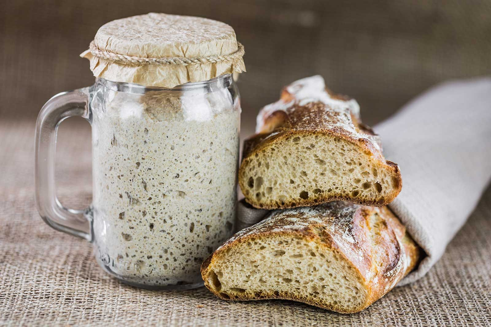 A jar of sourdough starter sitting next to some sourdough baguettes.