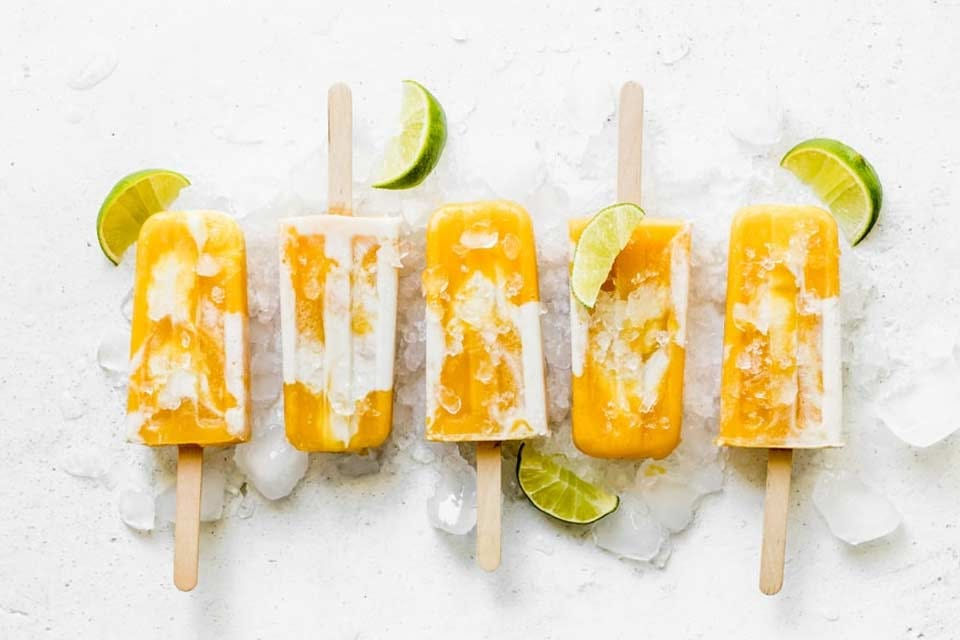 Five mango Popsicles surrounded by ice cubes and limes.
