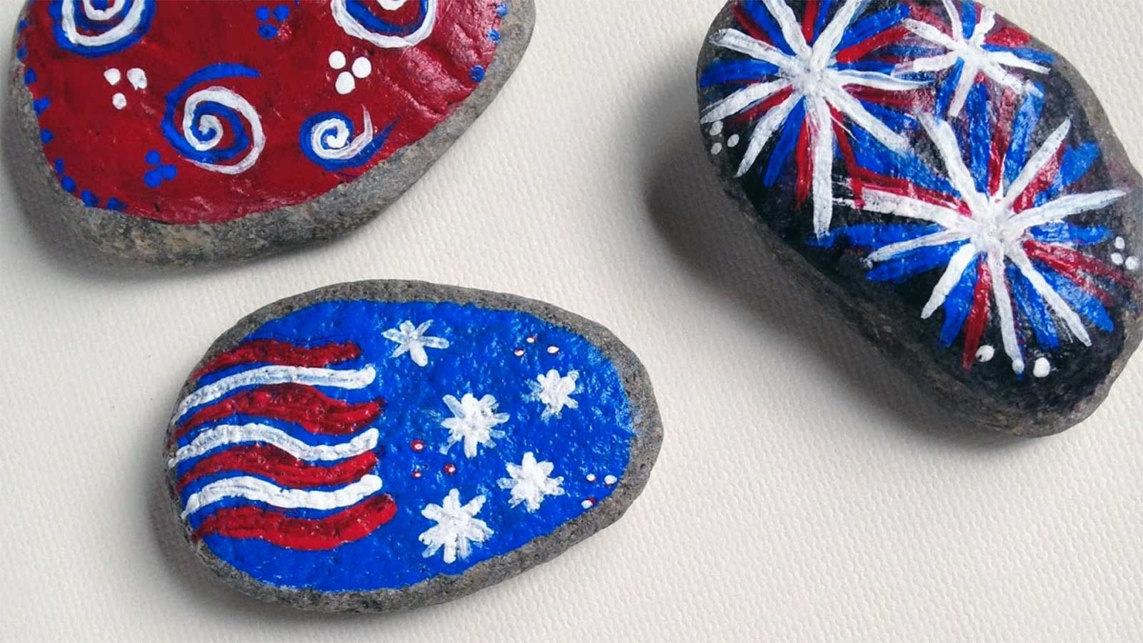 Three rocks painted with a Fourth of July theme.