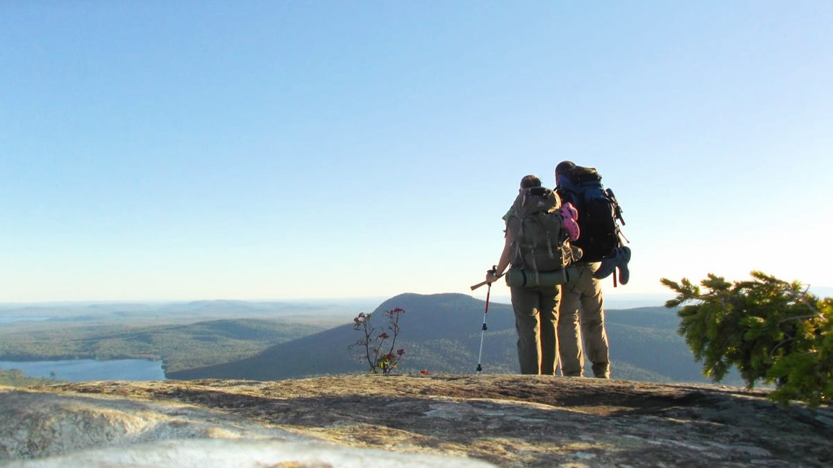 Two hikers looking out at breathtaking views, with there backpacks on.