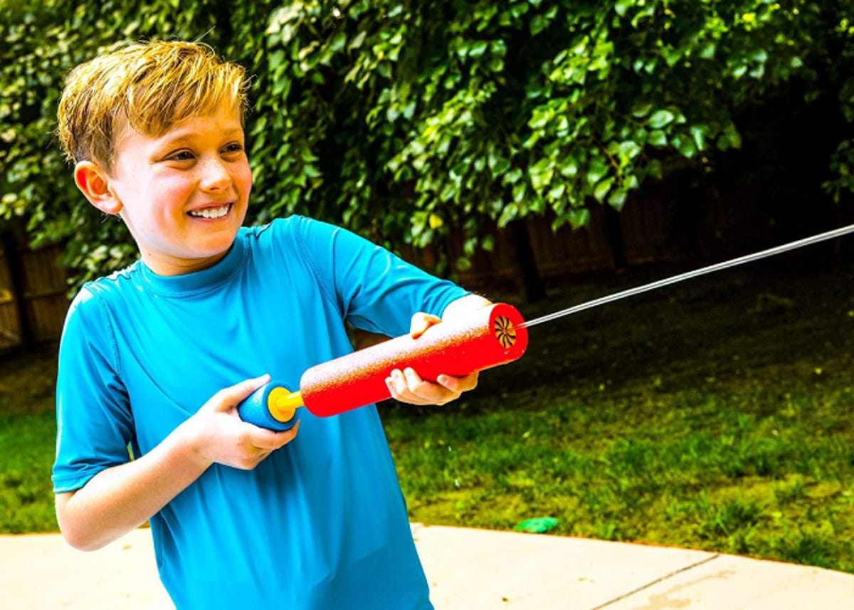 a smiling boy with a foam water blaster shooting a stream of water outside