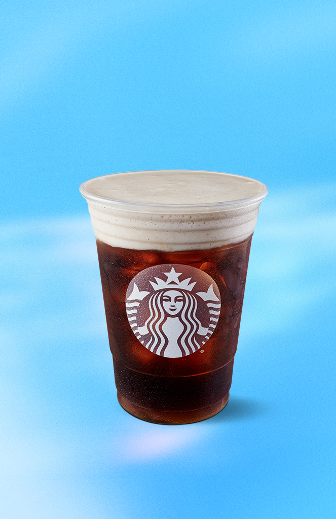 Starbucks new cold brew drink sits in front of a blue and white cloud background.