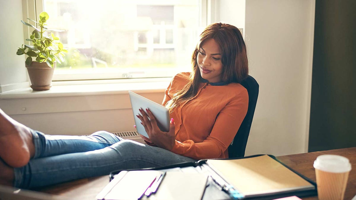 A woman sitting in an office chair with her feet up on the desk as she looks at an iPad.