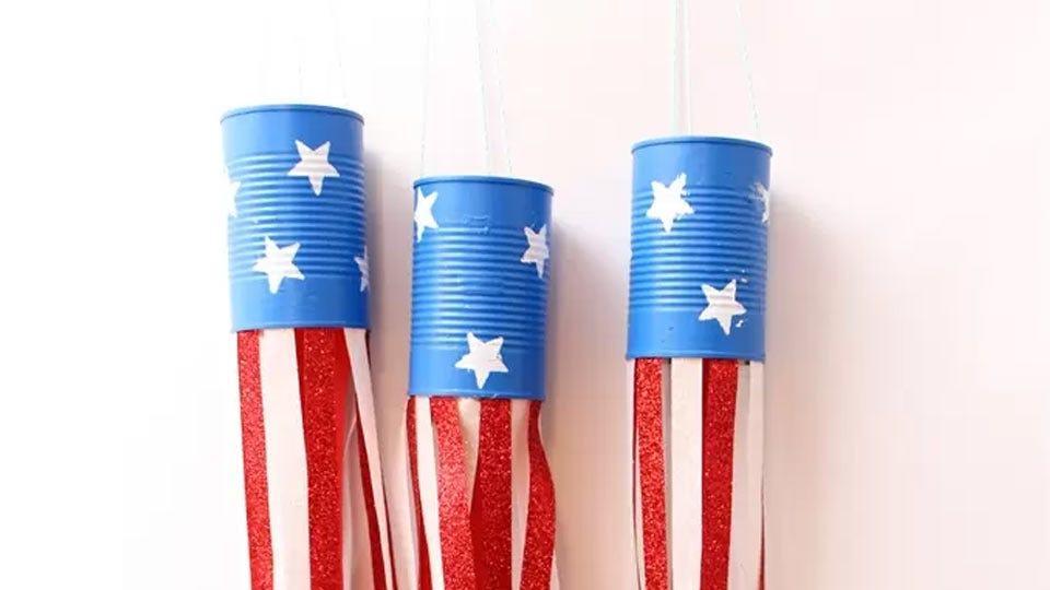 Three tin can windsocks decorated like American flags.