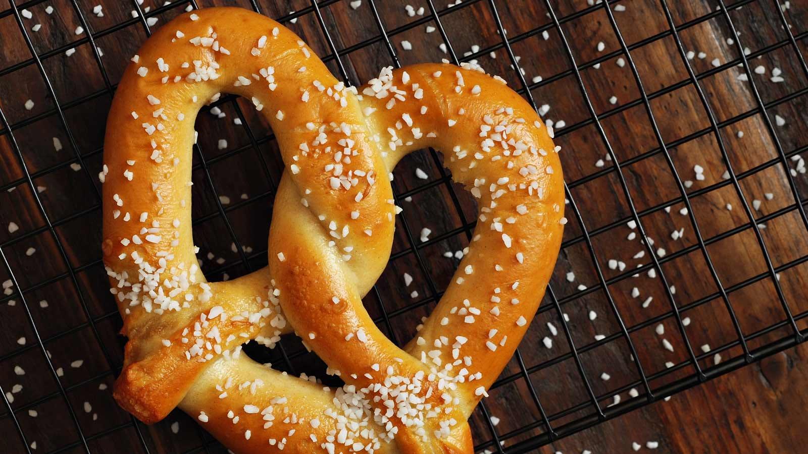 A fresh soft pretzel, sprinkled with salt.