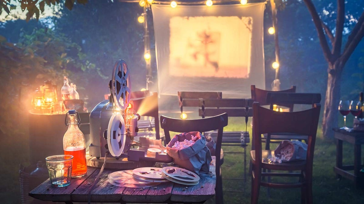 A reel-to-reel movie projector showing a film on a sheet in a backyard.