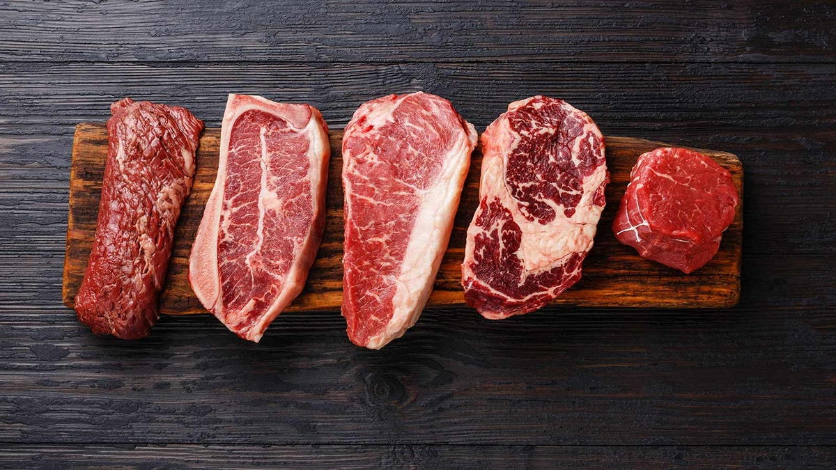 Five different kinds of steaks lined up on a cutting board.
