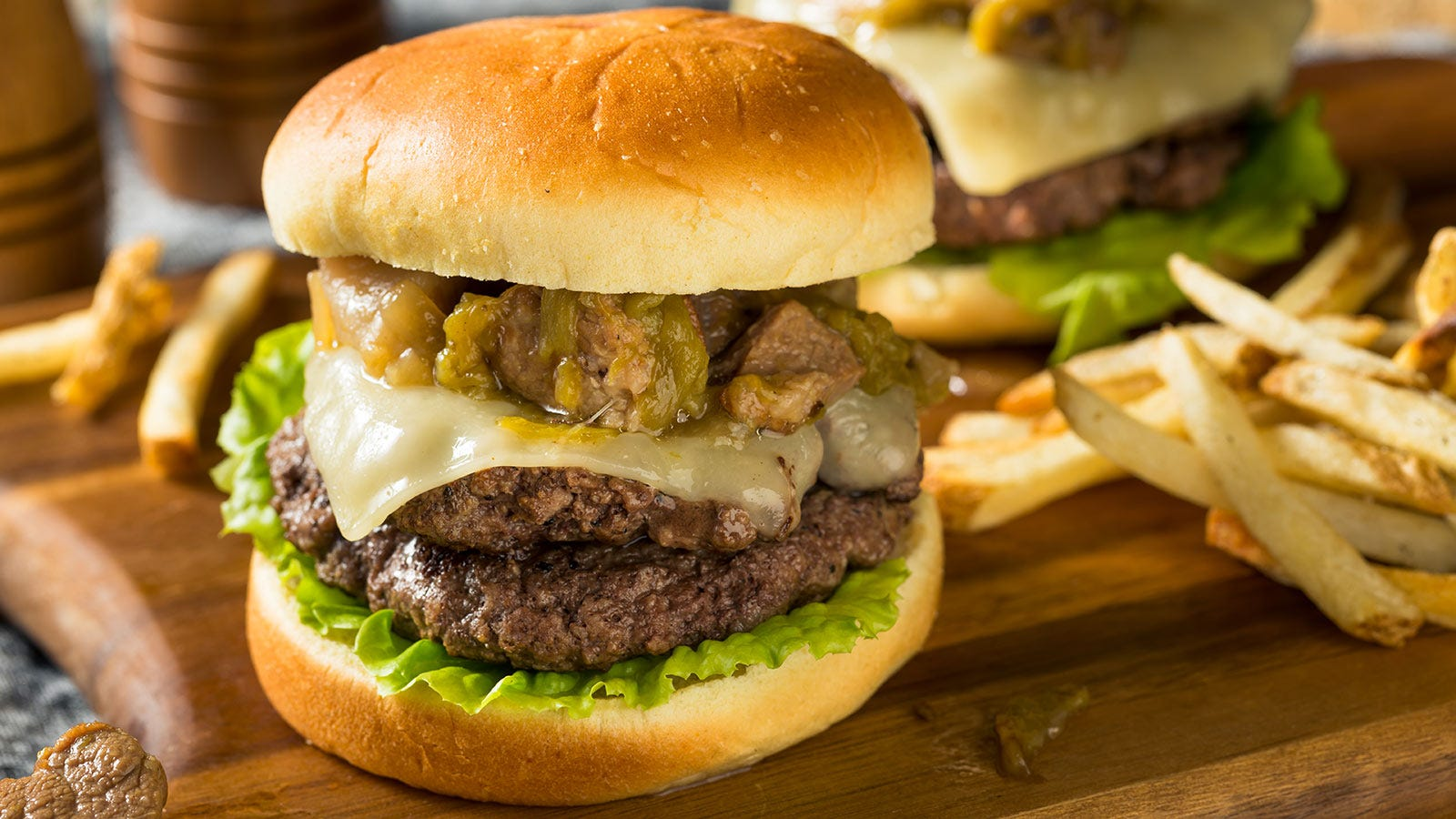 A sizable burger decked out with cheese and green chili sauce.