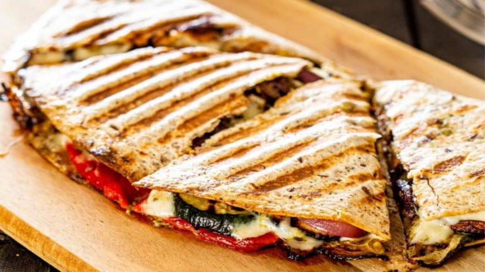 A hot quesadilla filled with grilled vegetables and melted cheese, sitting on a rustic cutting board.