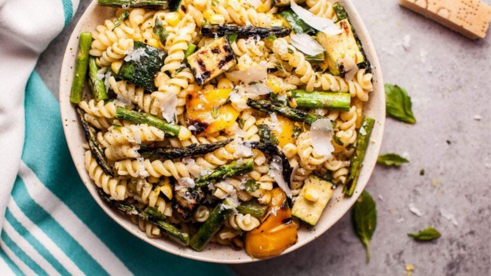 A cold bowl filled with rotini pasta salad full of grilled vegetables.