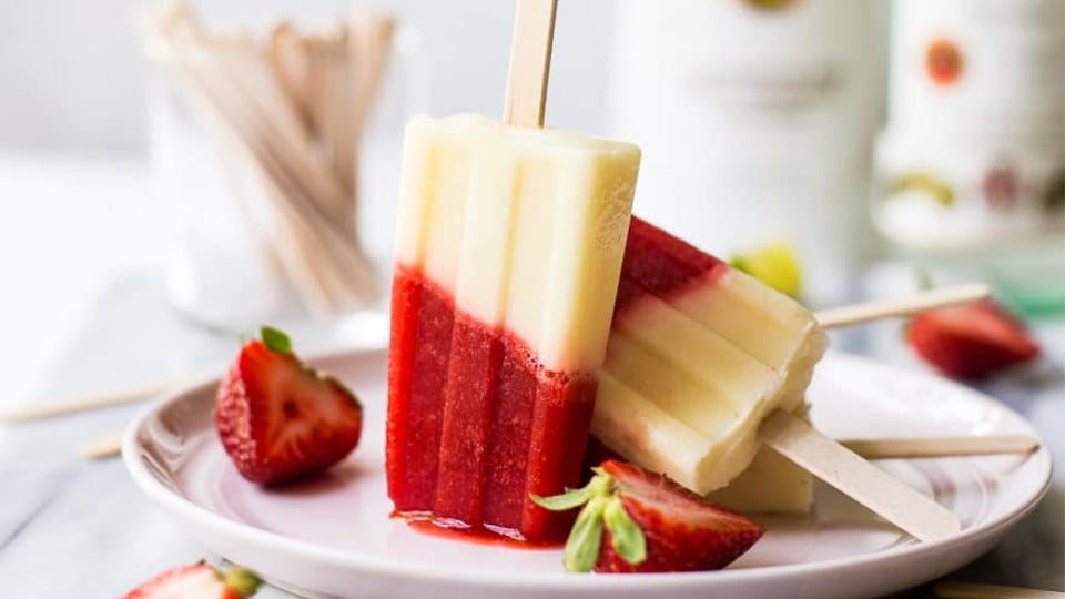 Three Miami Vice Popsicles sitting on a plate surrounded by strawberries.