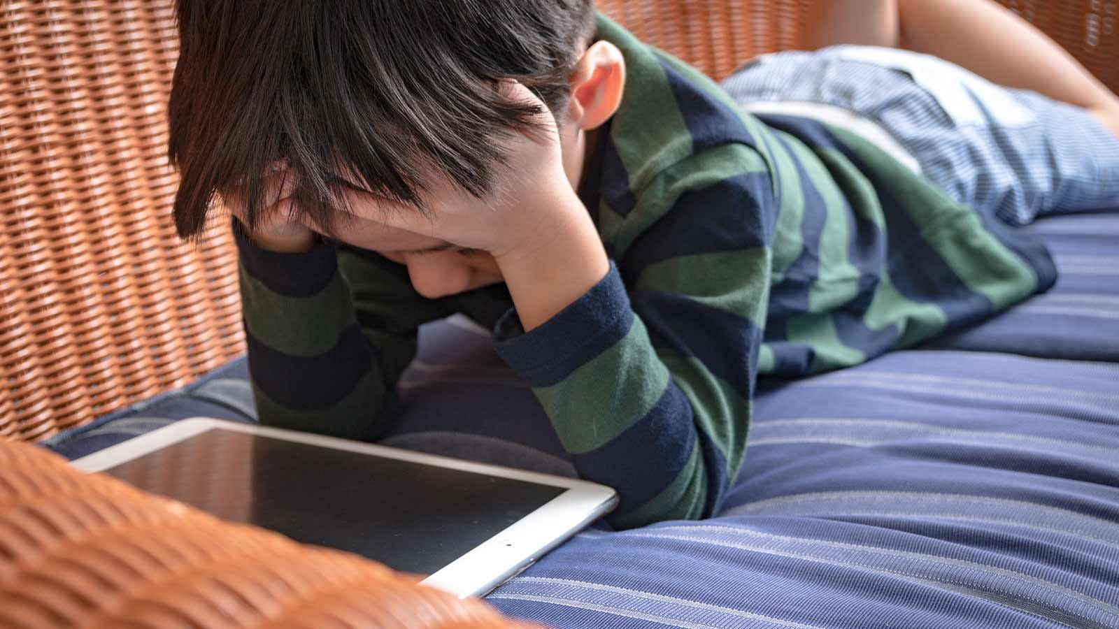 Young boy frustrated by the lack of physical activities during his virtual summer camp.