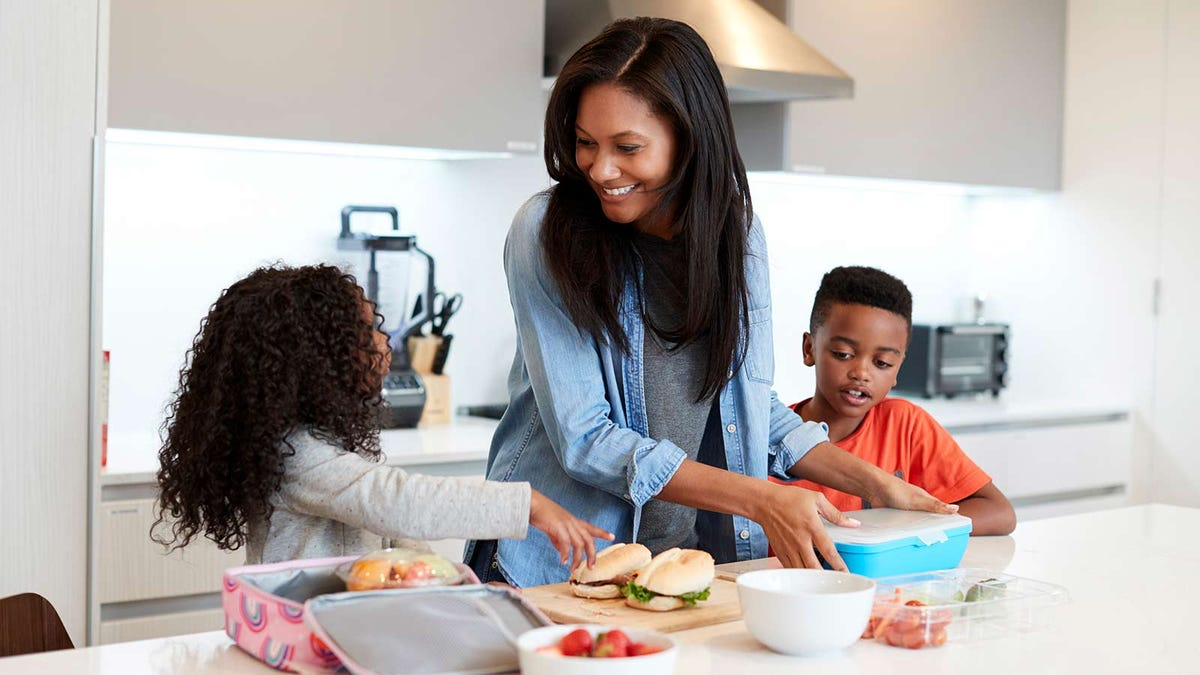 A mom packing lunches with her two children in a brightly lit kitchen.