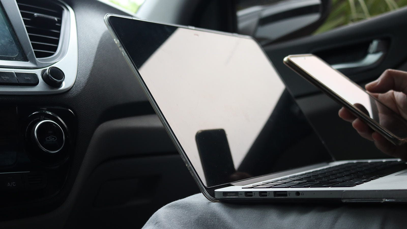 Someone working on a laptop and holding a smartphone in a car.