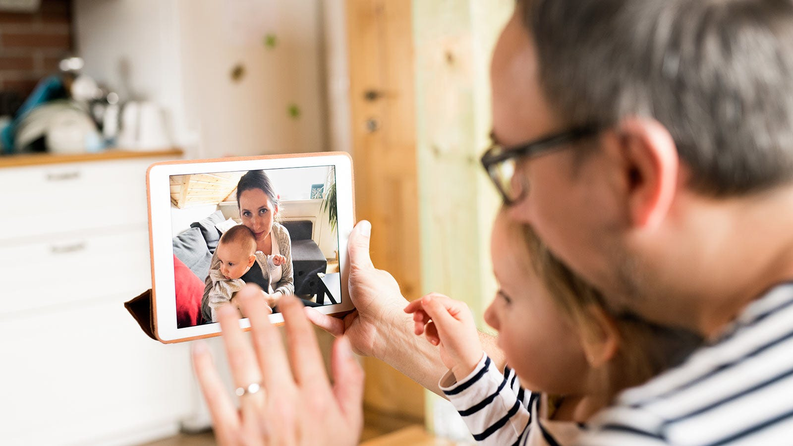 A man and little girl video chatting on a tablet with a woman holding a baby.