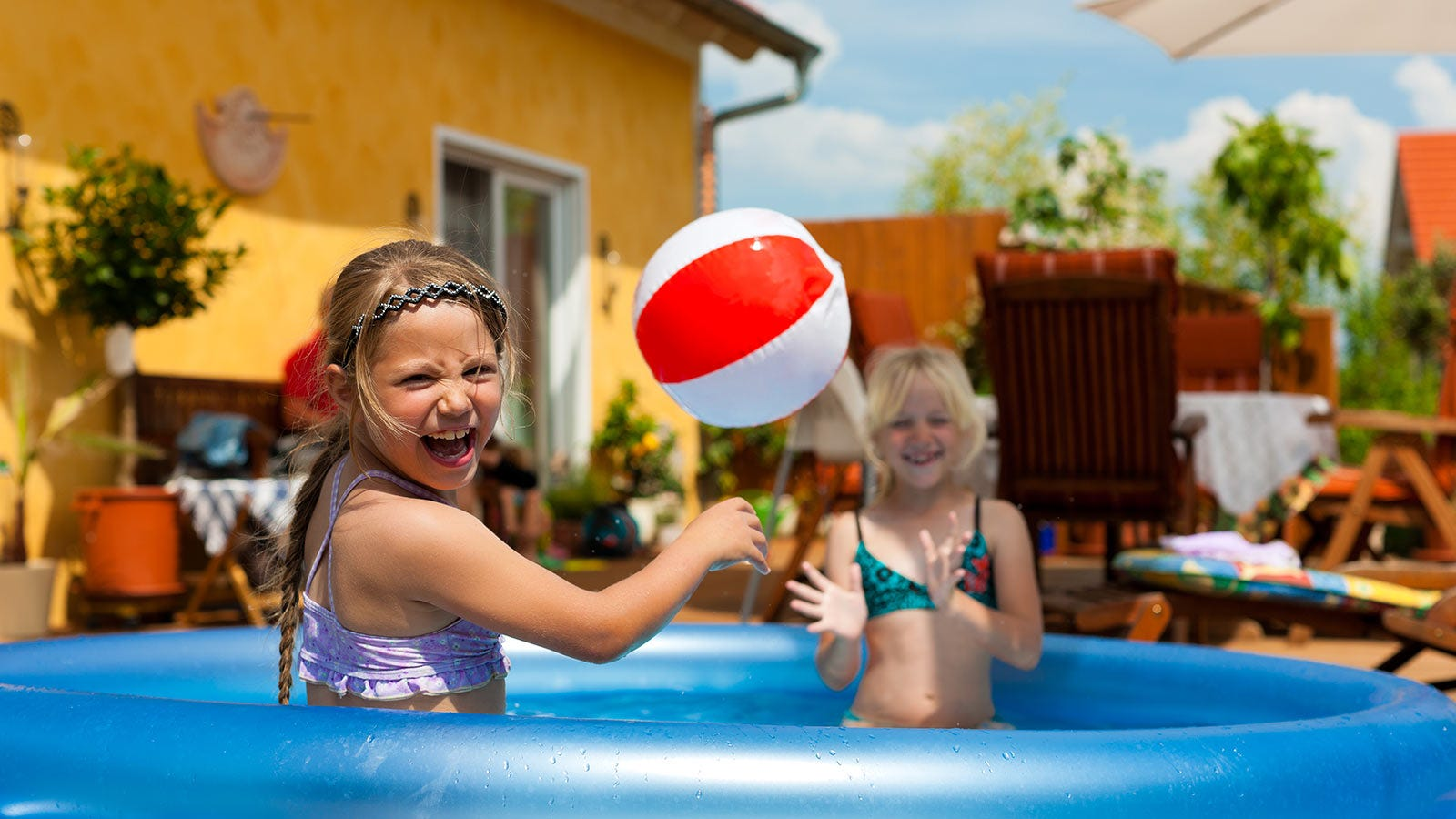 Two little girls playing with a beach ball in an inflatable pool.