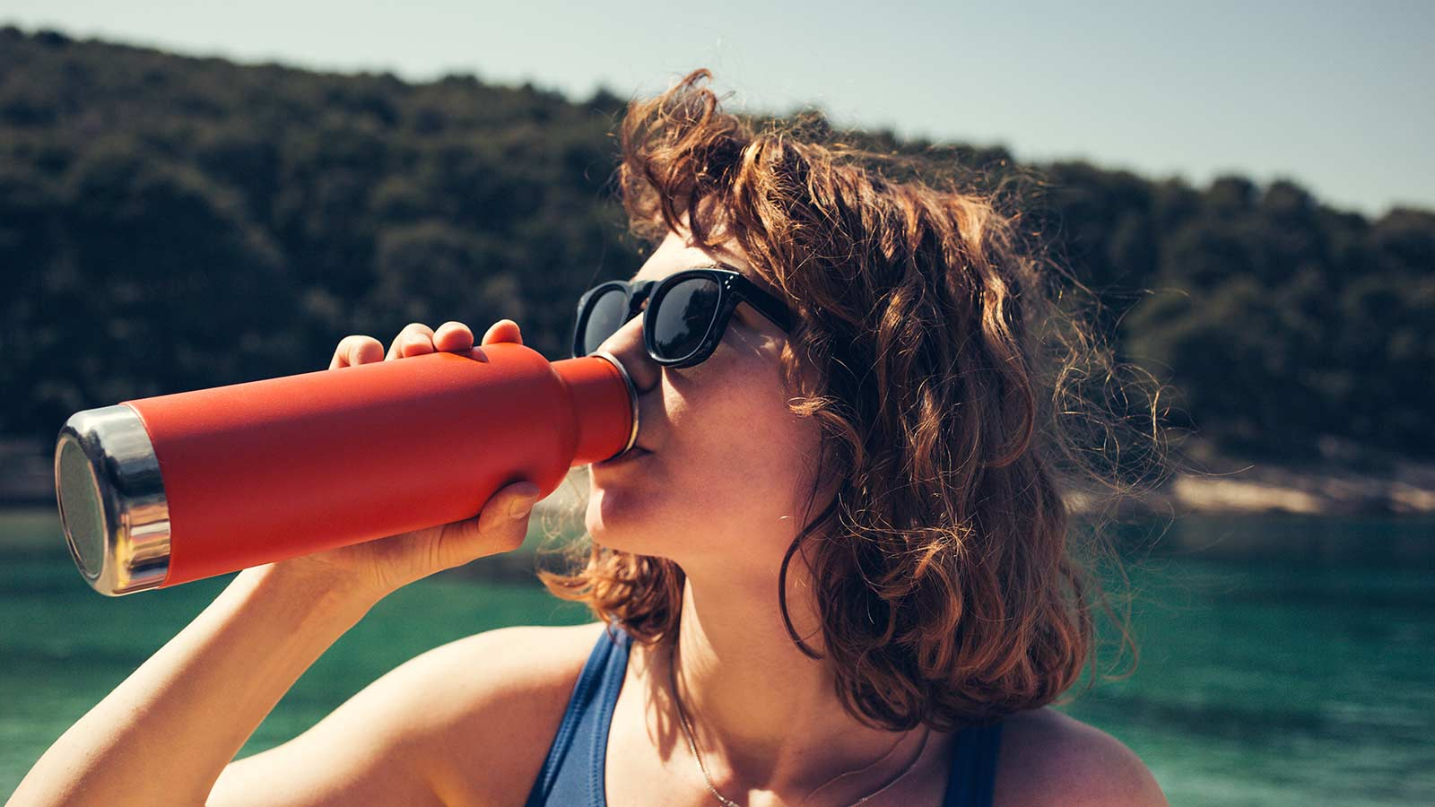 Woman drinking out of a steel water bottle.
