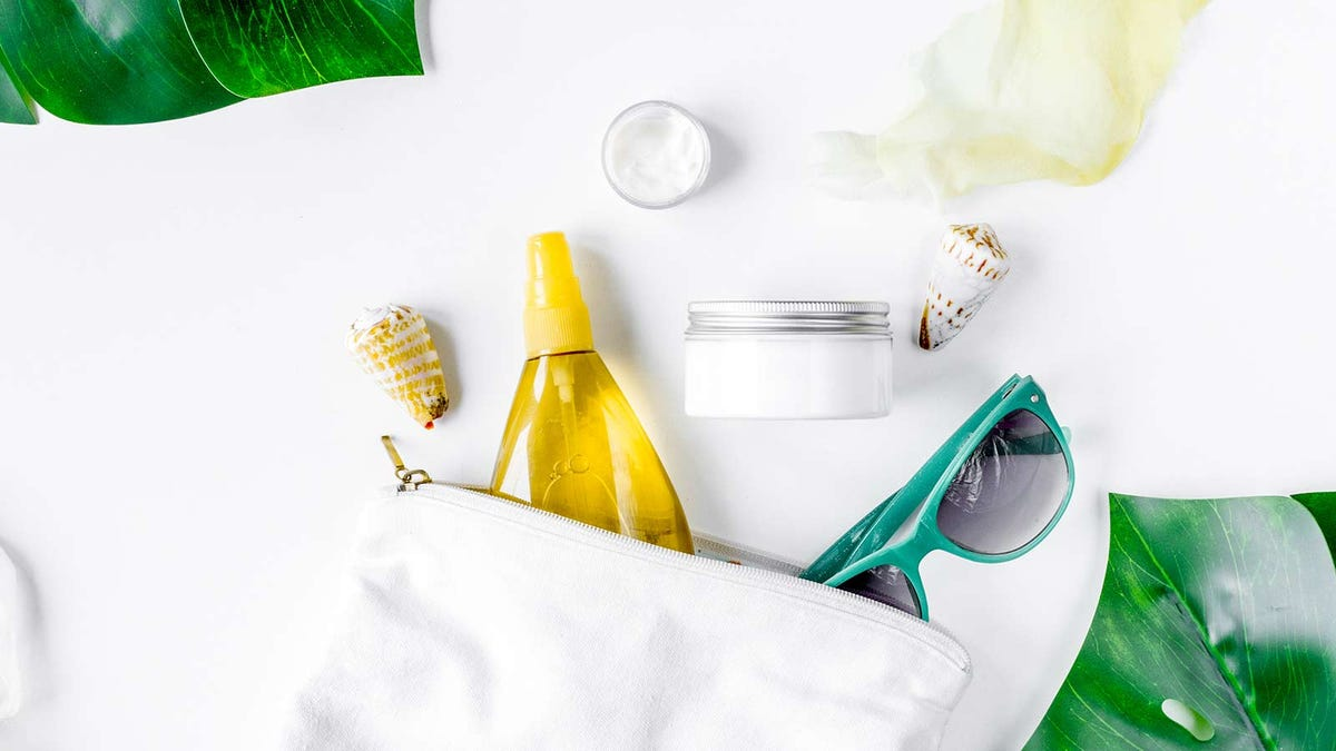 Skin cream and sprays, next to some sunglasses and sea shells on a white counter.