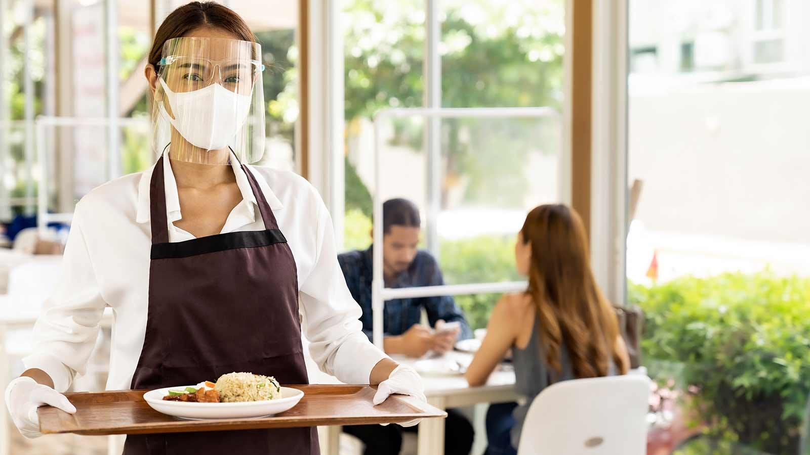Woman serving food in a company cafeteria wearing protective equipment.