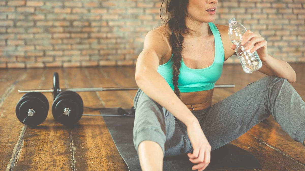 A woman sitting on a yoga mat next to some weights and holding a water bottle.