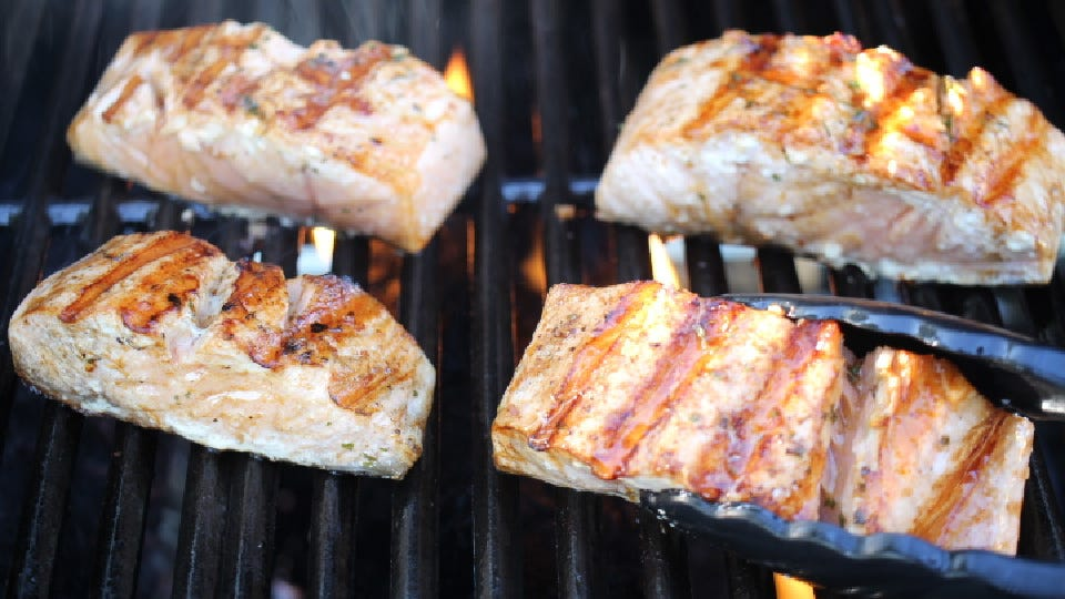Flipping salmon filets using a pair of tongs.
