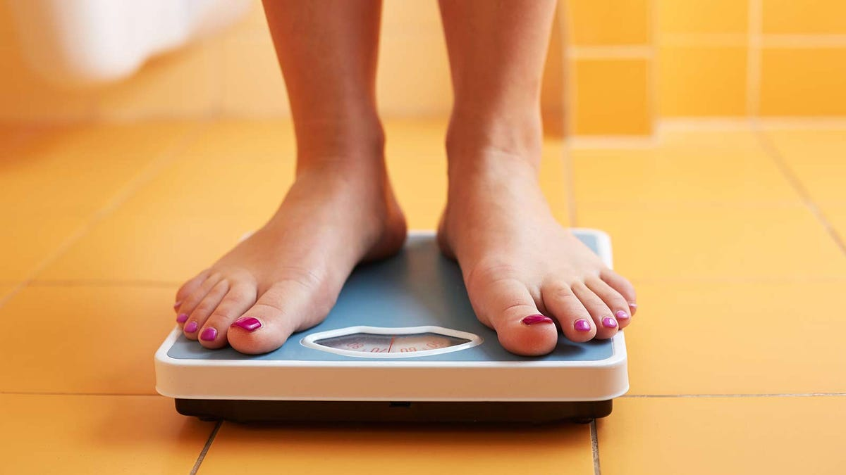 A woman standing on a bathroom scale at home, checking her weight.