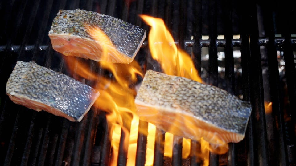 A spike of flame after placing marinated salmon filets on the grill.