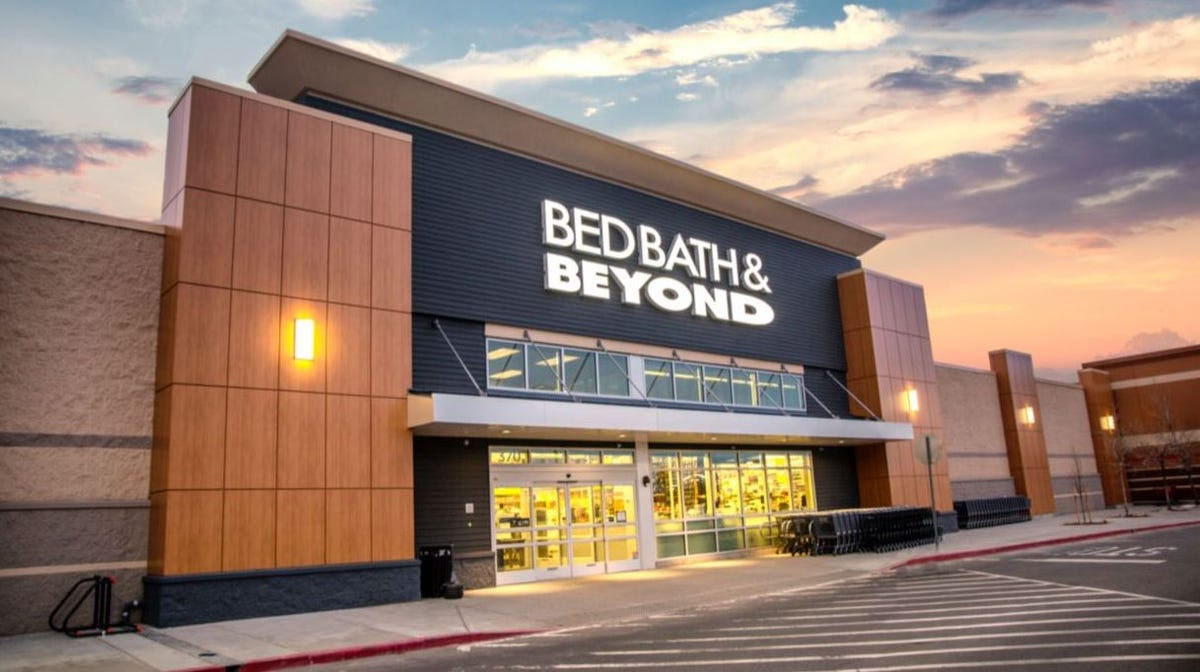 The exterior of a Bed Bath & Beyond storefront as seen at sunset.