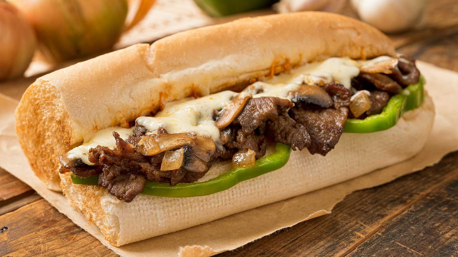 A steak submarine sandwich with melted cheese, onions, and green peppers.
