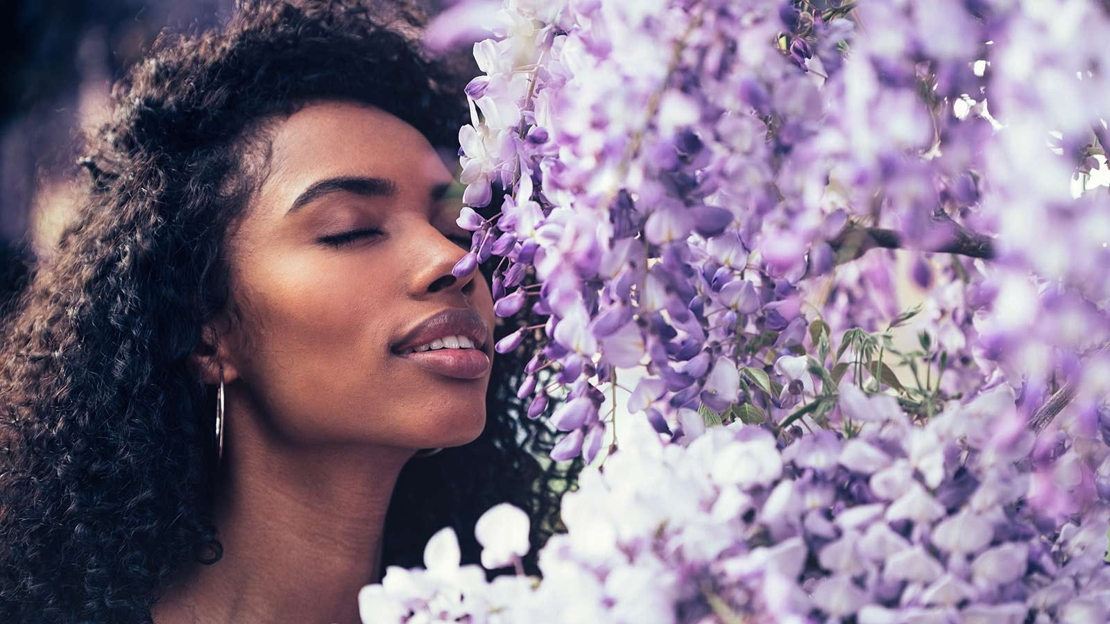 A woman smelling flowers.