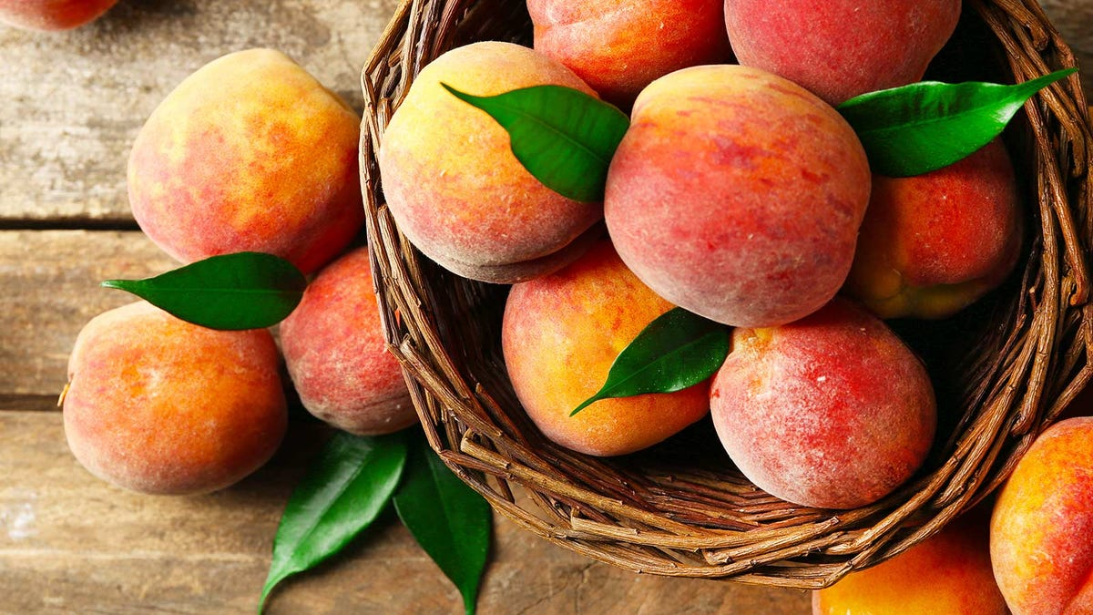A basket of peaches on a wood table.