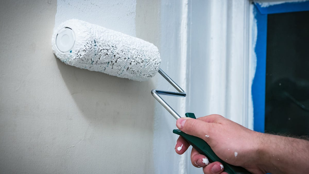 A person using a paint roller to prime the walls of a room before applying the actual paint.