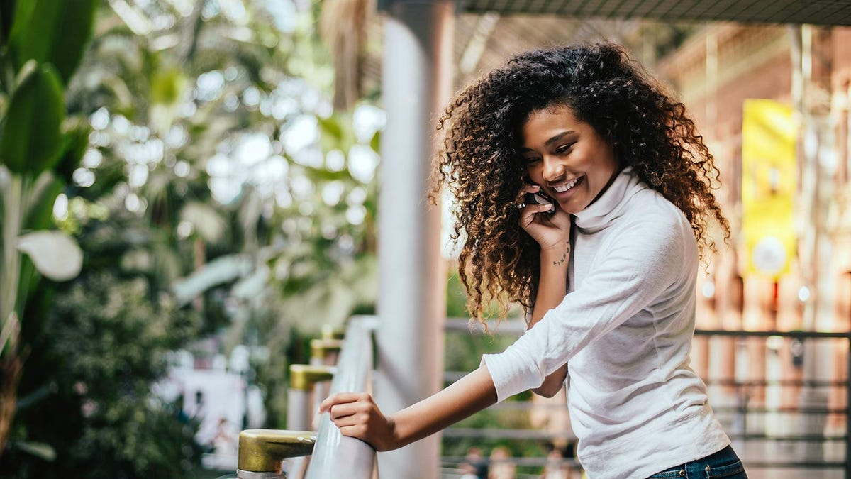 A woman smiling while talking on the phone outside on her balcony.