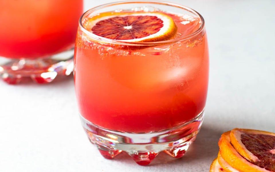 Two glasses filled with blood orange mocktails, garnished with a gorgeous citrus slice.