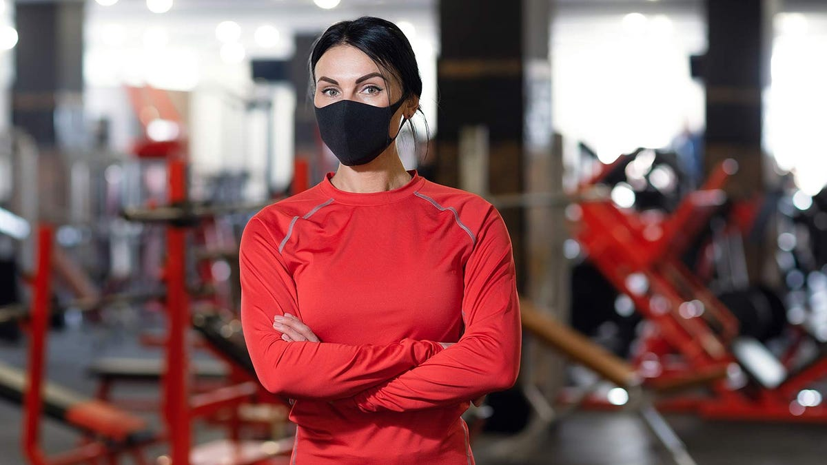 A woman wearing a face mask in a gym.
