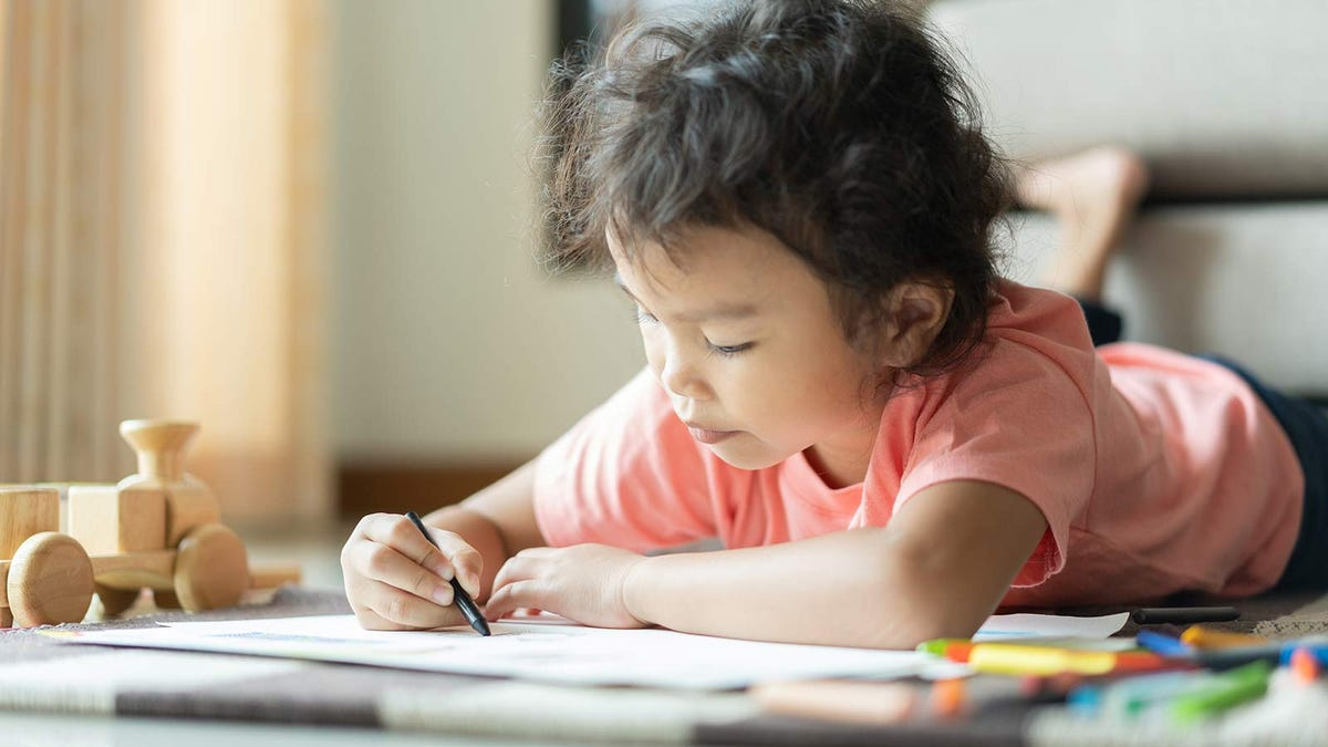 A young child lying on the floor and coloring during quiet time.