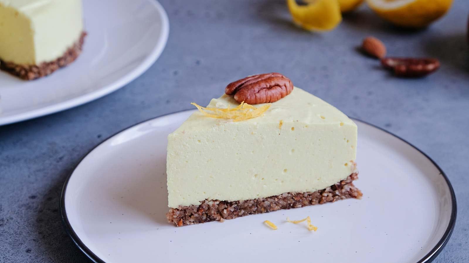 A slice of raw vegan lemon cheesecake on a white plate.