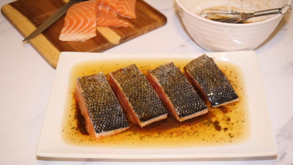 Marinating salmon filets in a homemade marinade with salmon scraps and marinade in the background.