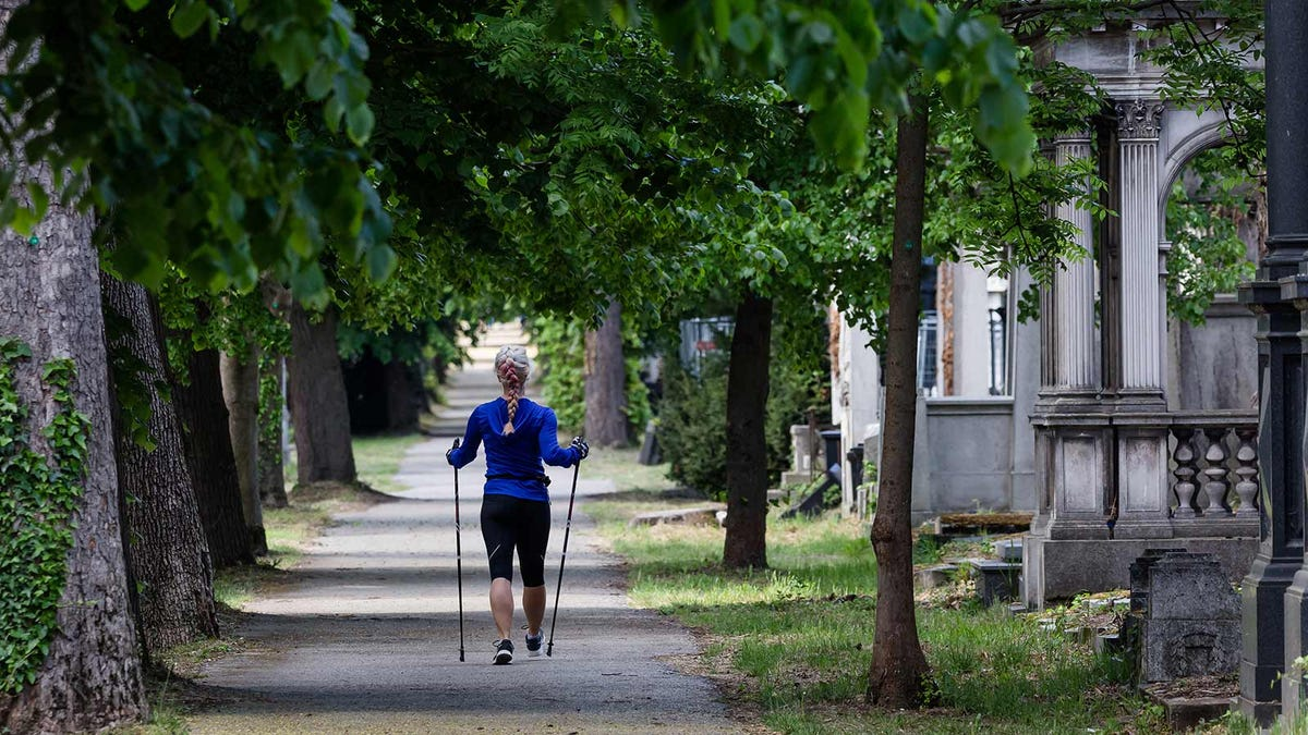 A woman in exercise clothes walking through a cemetery with walking sticks.