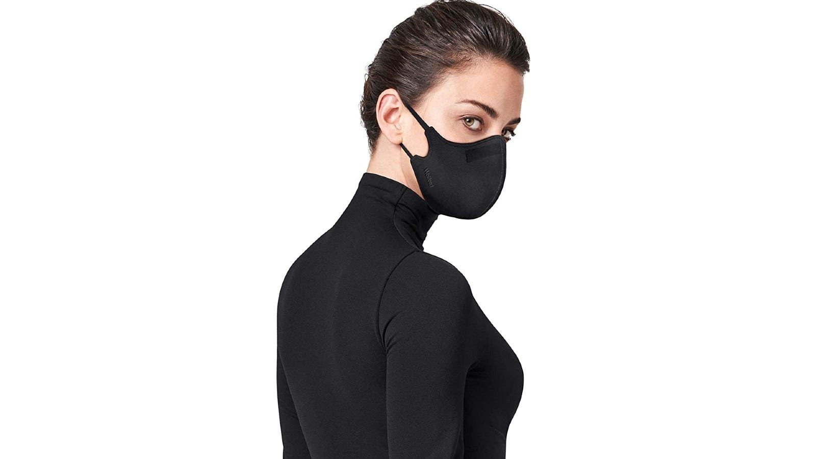 A woman wearing the Wolford Stay Safe Face Mask in black.