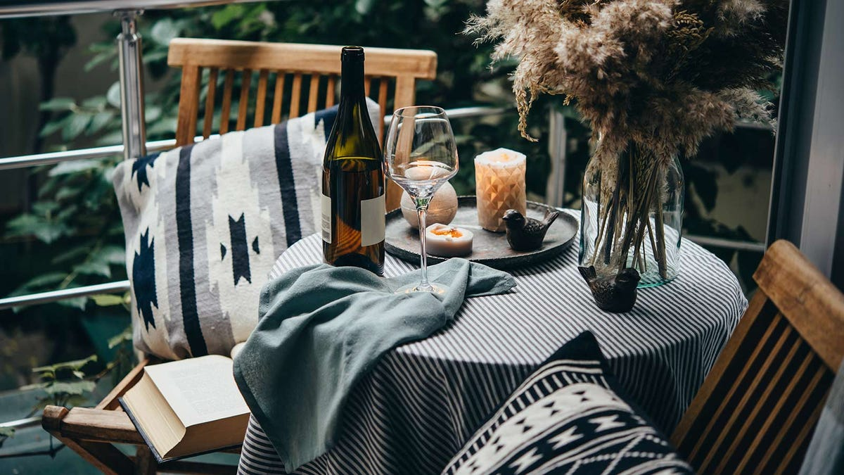 A bistro table with a bottle of wine and wine glass sitting on it, and two chairs.