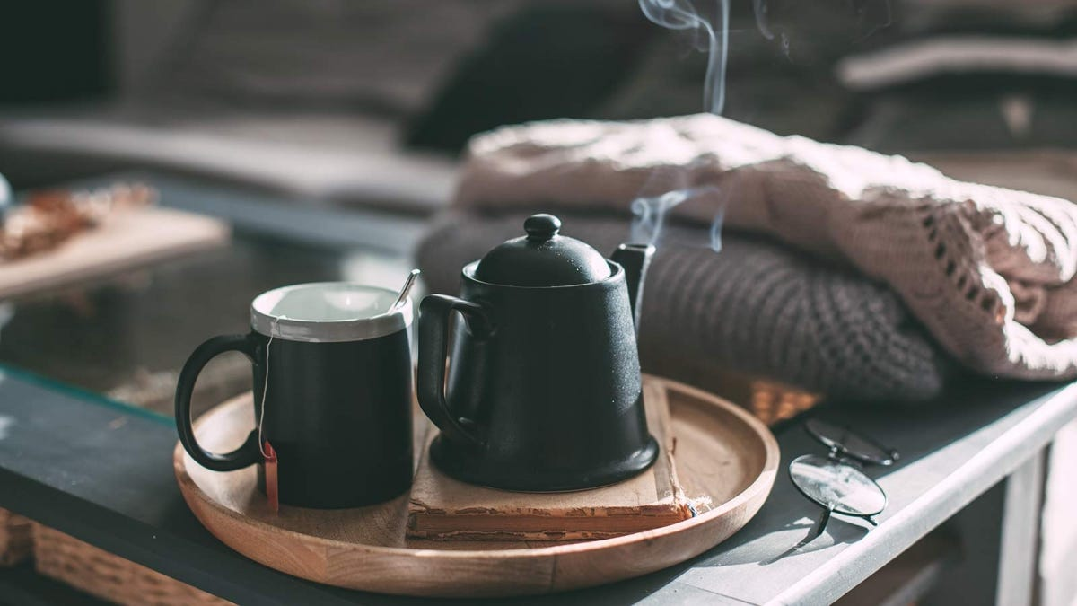 A steaming kettle sits next to a cup of tea on a wooden tray.