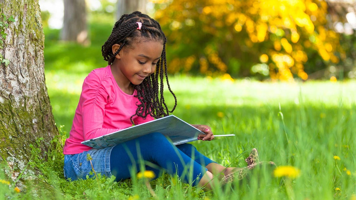 A little girl sitting under a tree and reading a book.